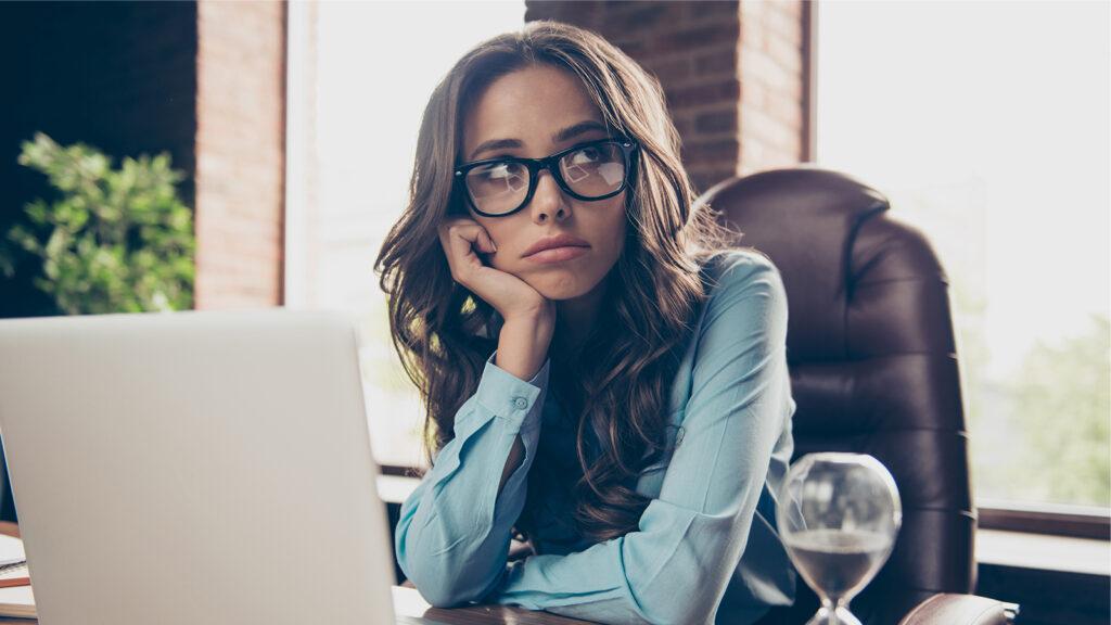不安げな表情でパソコンの前に座っている女性の画像